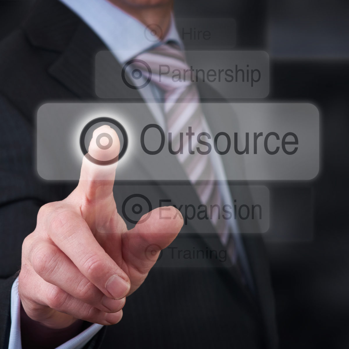 A businessman Pointing to a business outsourcing button on a clear screen.